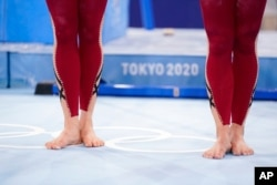FILE - German gymnasts wear unitards and wait to perform during the women's artistic gymnastic qualifications at the 2020 Summer Olympics, in Tokyo, July 25, 2021.
