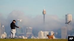 FILE - A man gestures to his dog as fog drifts through the buildings in Sydney's central business district, Australia, June 11, 2021.