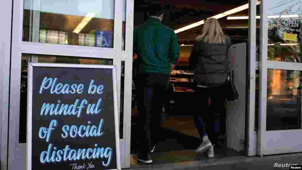 """미국 워싱턴주 시애틀의 가게 앞에 """"사회적 거리를 둘 것을 부탁드립니다""""가 적힌 안내판이 세워져 있다."""