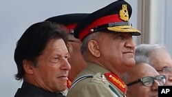 In this March 23, 2019 photo, Pakistan's Army Chief Gen. Qamar Javed Bajwa, center, watches a parade with Prime Minister Imran Khan, left, and President Arif Alvi, in Islamabad, Pakistan. Khan is keeping his powerful army chief in place for another…
