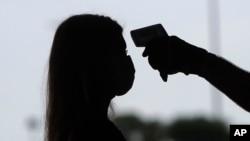 Seorang perempuan sedang diperiksa suhunya untuk mencegah penyebaran penyakit Covid-19 di Arlington, Texas, 1 Juni 2020.