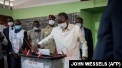 Le président de la Guinée, Alpha Condé vote dans les urnes lors des élections présidentielles à Conakry le 18 octobre 2020.