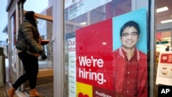A passer-by walks past an employment hiring sign at a Target store, Feb. 9, 2021, in Westwood, Massachusetts. (AP)