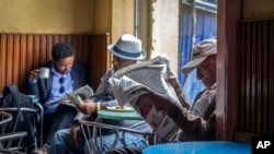 FILE - In this Oct. 10, 2016 file photo, Ethiopian men read newspapers during a declared state of emergency and internet shutdown in Addis Ababa, where the lawmakers on Feb. 13, 2020 approved a controversial law aimed at curbing hate speech.