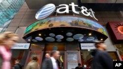 En esta fotografía de archivo del 21 de octubre de 2014, la gente pasa frente a una tienda de AT&T en Times Square de Nueva York.
