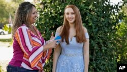 Annette Reynolds, left, puts the finishing touches on her daughter Amanda's hair as she poses for a photo in her prom gown outside their home in Largo. She will miss her high school graduation and senior prom due to the coronavirus outbreak.