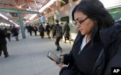 FILE - Marilu Rodriguez checks a news website on her smartphone before boarding a train home at the end of her workweek in Chicago, March 13, 2015.