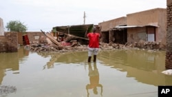 FILE - A man gestures as he wades through a flooded road in the town of Salmaniya, about 35 km southwest of the capital, Khartoum, Sudan, Sept. 17, 2020.