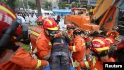 Rescue workers move a casualty at the site of a hotel being used for the coronavirus quarantine collapsed, in the southeast Chinese port city of Quanzhou, Fujian province, China, March 8, 2020.