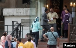"""People wait outside a bakery and pastry shop named """"The Baker"""" and known as """"El Khabaz,"""" for traditional Eid al-Fitr festivities sweets and biscuits, amid concerns over the coronavirus disease, in the Cairo suburb of Maadi, Egypt, May 21, 2020."""