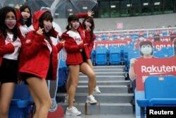 Cheerleaders take group photos with face masks on at the first professional baseball league game of the season at Taoyuan International baseball stadium in Taoyuan city, Taiwan, April 11, 2020.