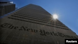 FILE - The sun peaks over the New York Times building in New York, Aug. 14, 2013.