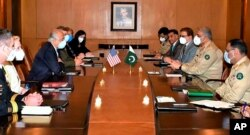 In this photo released by Pakistan's military, a U.S. delegation headed by peace envoy for Afghanistan, Zalmay Khalilzad, third left, hold talks with Pakistan's army chief, Gen. Qamar Javed Bajwa, second right, in Rawalpindi, Sept. 14, 2020.