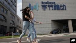 在北京,行人戴著口罩走過擁有抖音/TikTok的字節跳動公司的總部。(2020年8月7日)