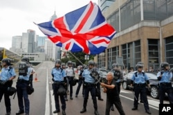 FILE - A woman waves a British flag as policemen in anti-riot gear stand guard against protesters on a closed-off road near the Legislative Council in Hong Kong, June 12, 2019.