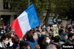 Orang-orang berkumpul di Place de la Republique di Paris, untuk memberi penghormatan kepada Samuel Paty, guru bahasa Prancis yang dipenggal, Paris, 18 Oktober 2020. (Reuters)