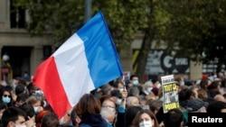 ປະຊາຊົນຢູ່ຈະຕຸລັດ Place de la Republique ໃນນະຄອນຫຼວງ ປາຣີ, ສະແດງຄວາມນັບຖືຕໍ່ທ່ານ ຊາມູແອລ ປາຕີ, ນາຍຄູຊາວ ຝຣັ່ງ ທີ່ຖືກຂ້າຕັດຫົວຢູ່ຖະໜົນຂອງເມືອງ ກົງຟລັງ ແຊັງ ໂອໂນຣີນ ຢູ່ເຂດຊານເມືອງ ຂອງນະຄອນຫຼວງ ປາຣີ. 18 ຕຸລາ, 2020. (Reuters)