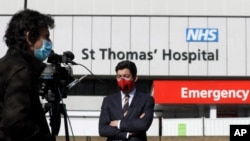 Journalists work outside St Thomas' Hospital in central London as British Prime Minister Boris Johnson was moved to intensive care after his coronavirus symptoms worsened in London, Tuesday, April 7, 2020. Johnson was admitted to St Thomas' hospital…