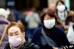 FILE - Pedestrians wear protective masks in Tokyo, Jan. 16, 2020.