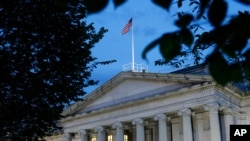 FILE - This June 6, 2019, photo shows the U.S. Treasury Department building at dusk in Washington.