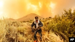 David Garfield clears a fire break around his home as the Sugar Fire, part of the Beckwourth Complex Fire, burns toward Doyle, Calif., July 10, 2021.