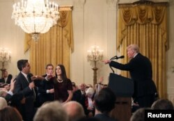 FILE - A White House staff member reaches for the microphone held by CNN's Jim Acosta as he questions U.S. President Donald Trump during a news conference at the White House in Washington, Nov. 7, 2018.