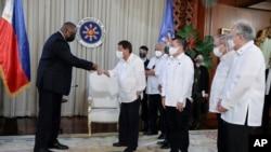 Menteri Pertahanan AS Lloyd Austin (kiri) bersalaman degan Presiden Filipina Rodrigo Duterte dalam pertemuan di Istana Malacanang, 29 Juli 2021.