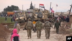 In this frame grab from video, Russian, Syrian and others gather next to an American military convoy stuck in the village of Khirbet Ammu, east of Qamishli city, Syria, Feb. 12, 2020.