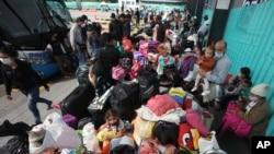 Migrantes venezolanos esperan un autobús para viajar a la frontera, luego de levantar su campamento en Bogotá, Colombia, el jueves 2 de julio de 2020.
