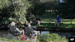 FILE - Neighbors chat across a stream as they practice social distancing in a suburb of Christchurch, New Zealand, Apr. 5, 2020.