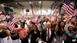 FILE - People hold flags as they are sworn in as U.S. citizens during a naturalization ceremony in Phoenix, Arizona.