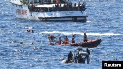 FILE - Migrants swim after jumping off the Spanish rescue ship Open Arms, close to the Italian shore in Lampedusa, Italy, Aug. 20, 2019.