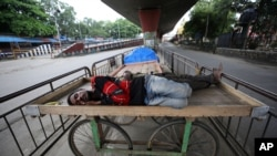 Homeless men sleep on a handcart parked on a road divider in a containment zone during lockdown in Bengaluru, India, Sunday, July 5, 2020. India's coronavirus caseload is fourth in the world behind the U.S., Brazil and Russia. (AP Photo/Aijaz Rahi)