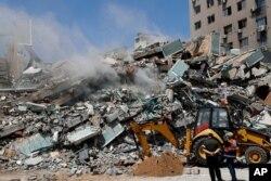 Wafanyakazi wakiondoa kifusi cha jengo lililoshambuliwa na ndege za kijeshi za Israeli Jumamosi lililokuwa na ofisi za shirika la habari la The Associated Press, broadcaster Al-Jazeera na vyombo vya habari vinginevyo, mjini Gaza, Jumapili, Mei 16, 2021. (AP Photo/Adel Hana)