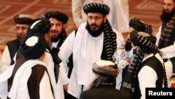 FILE - Taliban delegates speak during talks between the Afghan government and Taliban insurgents in Doha, Qatar, Sept. 12, 2020.