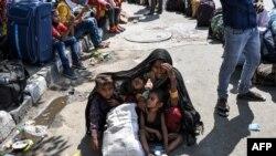 Una mujer cubre a sus hijos con un manto mientras esperan con otros trabajadores migratorios poder inscribirse para abordar un tren a casa.