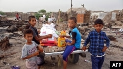 FILE - Internally displaced Yemenis whose camp was ravaged by fire two days earlier receive food aid in the village of al-Durayhimi, on the southern edge of the flashpoint Red Sea port city of Hodeida, July 19, 2021.