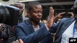 Malawian preacher Shepherd Bushiri waves at supporters as he leaves the Lilongwe Magistrate court, in Lilongwe, Malawi, Nov. 19, 2020.