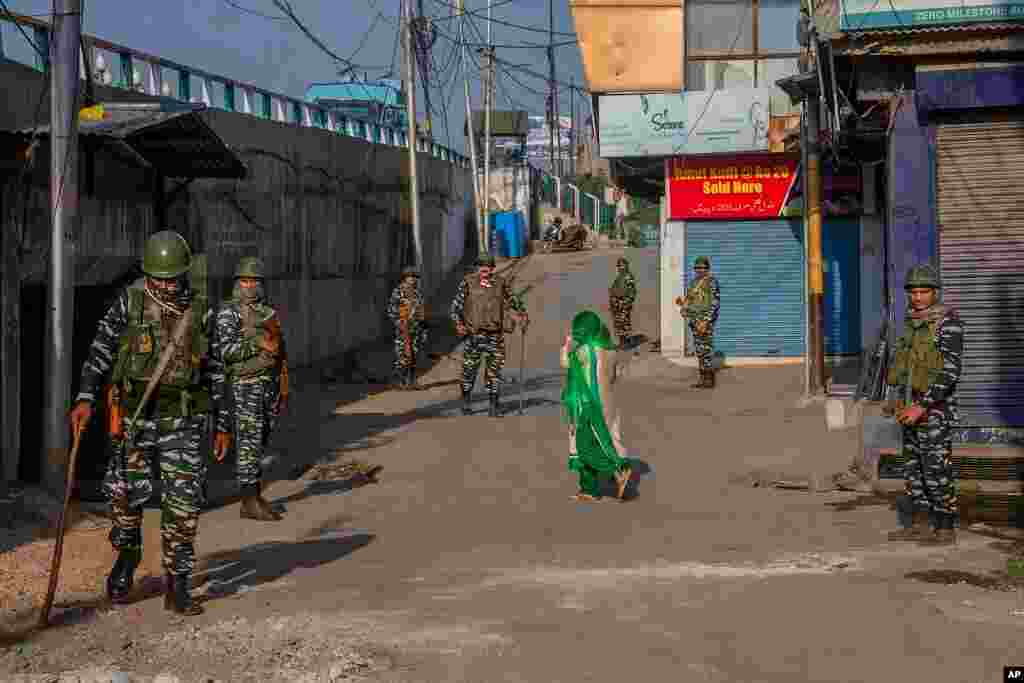 A Kashmiri woman covers her face as she walks past paramilitary soldiers standing guard in a closed market area in Srinagar, Indian controlled Kashmir. Indian authorities cracked down on public movement after the death Thursday of a top separatist leader.