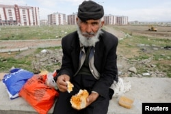 An Afghan migrant eats outside a bus terminal, as he and others struggle to find buses to take them to western Turkish cities, after crossing the Turkey-Iran border in April 11, 2018.