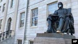 2020年3月14日馬薩諸塞州旅遊勝地劍橋哈佛大學的約翰·哈佛雕像戴上口罩。