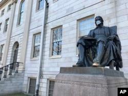 Patung John Harvard di Universitas Harvard, objek wisata populer di kampus di Cambridge, Massachusetts, didekorasi dengan topeng pelindung, 14 Maret 2020. (Foto: AP)