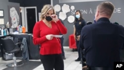 Salon owner Shelley Luther holds a citation and speaks with a Dallas police officer after she was cited for reopening her Salon A la Mode in Dallas, Texas , April 24, 2020.