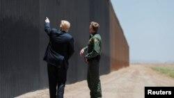 El presidente Donald Trump habla con el jefe de la Patrulla Fronteriza de EE.UU., Rodney Scott, frente a un segmento del muro fronterizo con México en San Luis, Arizona, el 23 de junio de 2020.