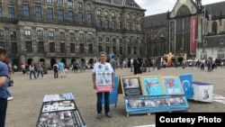 FILE - Abdurehim Gheni stands in demonstration with pictures of his relatives and other disappeared Uighurs, at Dam Square in Amsterdam in July. (Photo courtesy: Abdurehim Gheni)