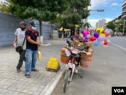 Soeung Tha sells balloons in front of Phnom Penh's Lanka Temple, Dec. 7, 2020. (Aun Chhengpor/VOA Khmer)