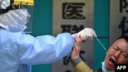 A man being tested for COVID-19 reacts as a medical worker takes a swab sample in Wuhan in China's central Hubei province on April 16, 2020.