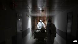 Para pekerja medis membawa seorang pasien virus corona ke unit perawatan intensif di Rumah Sakit Kota Filatov di Moskow, Rusia, 15 Mei 2020.