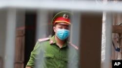 Một nhân viên công an canh giữ bên ngoài khu dân cư có dịch COVID-19 ở Hà Nội hôm 29/7. Bộ An ninh Nội địa Mỹ, được sự trợ giúp của Bộ Công an Việt Nam, vừa phá một đường dây lừa đảo qua mạng của người Việt trị giá gần 1 triệu USD liên quan đến đại dịch virus corona.