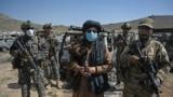 塔利班成员站在位于喀布尔东北部被摧毁的美国中央情报局 (CIA) 基地附近(法新社 2021年9月6日)